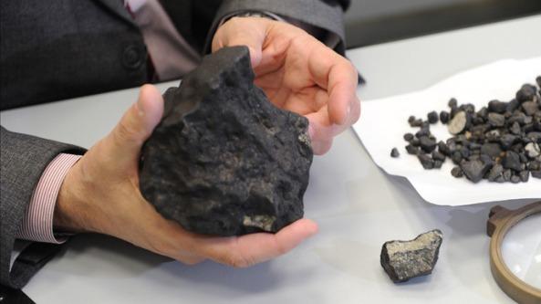 Victor Grokhovsky - lector la Institutul de Fizică și Tehnologie al Universității Federale Urali - cu fragmentul de meteorit găsit în timpul unei expediții în regiunea Chelyabinsk pe 25 februarie 2013. Credit: RIA Novosti / Pavel Lysizin.